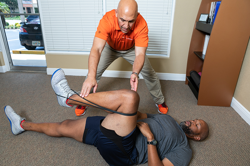Dr. Reza showing a client how to practice recovery at home