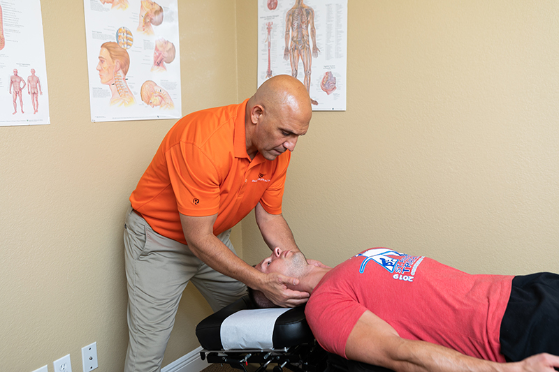 Dr. Reza performing neck chiropractic care on patient